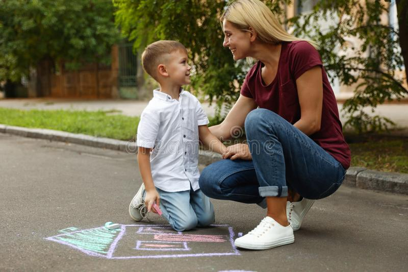 Nanny with cute little boy drawing house with chalks. On asphalt royalty free stock images