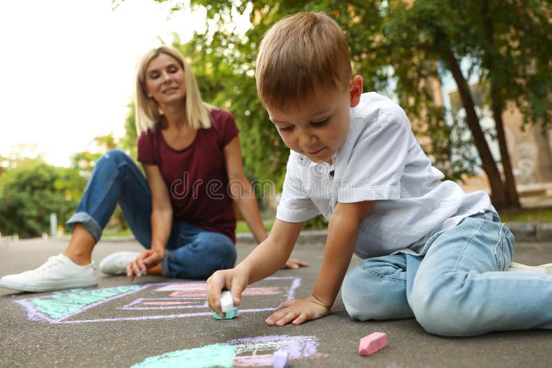 Nanny with cute little boy drawing house with chalks. On asphalt royalty free stock photos