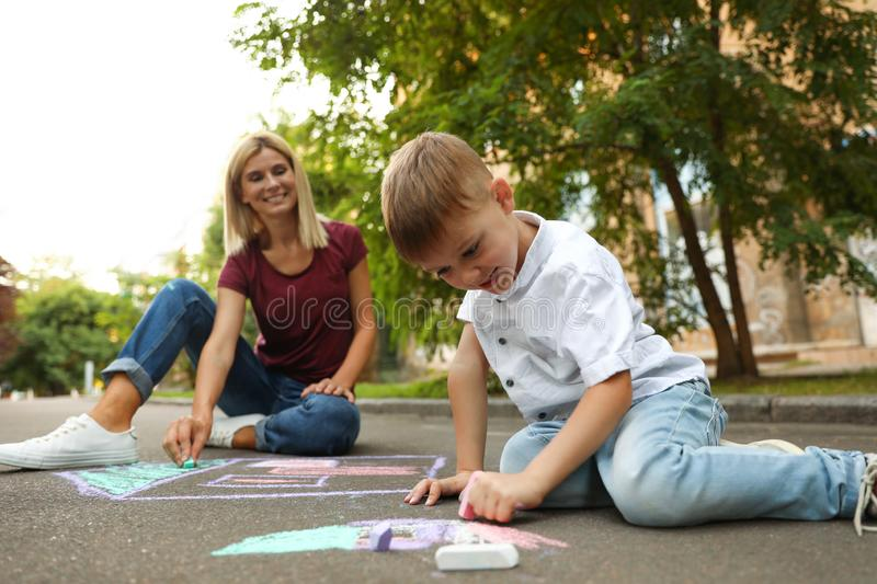Nanny with cute little boy drawing house with chalks. On asphalt royalty free stock photo