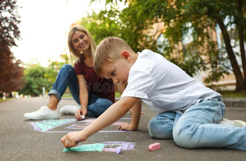 Nanny with cute little boy drawing house with chalks stock images