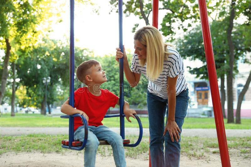 Nanny and cute little boy on  in park royalty free stock image