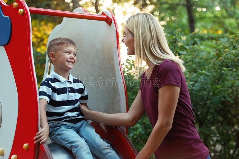 Nanny and cute little boy on slide royalty free stock photos