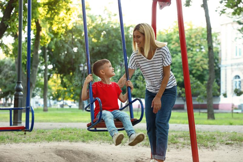Nanny and cute little boy on swing stock photos