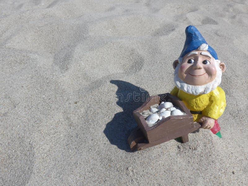 Nano divertente del giardino con la carriola sulla spiaggia fotografia stock