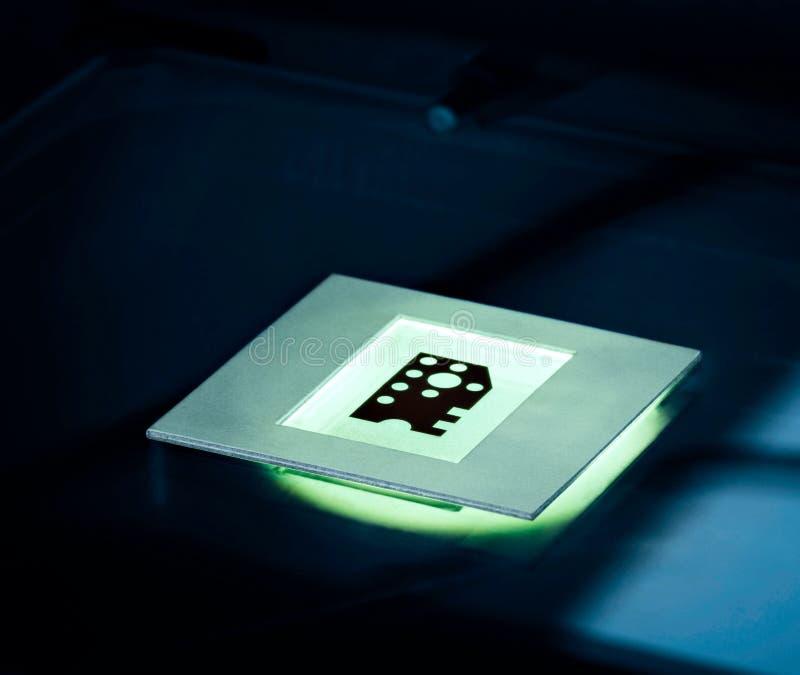 Nano teknologibegreppsbakgrund Mikrochipmatrisen som är upplyst på en mikroskoptabell i blått, tonar royaltyfria foton