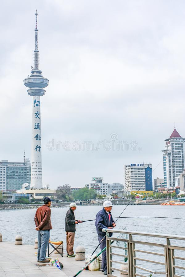 Nantong City / China - April 11, 2012 : Two Asian men fishing by the lake. One man hands behind hip standing behind looked on stock images