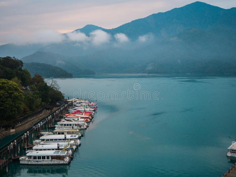 Sun Moon Lake shuttle boats at pier in a lake with mountain and clouds landscape. royalty free stock photos