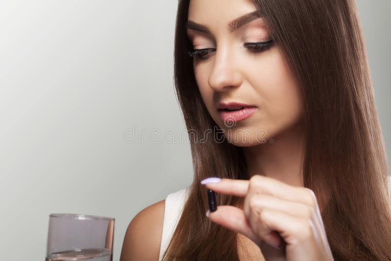Napój medycyny Ładna młoda kobieta która bierze czarnego h i pigułkę obraz stock