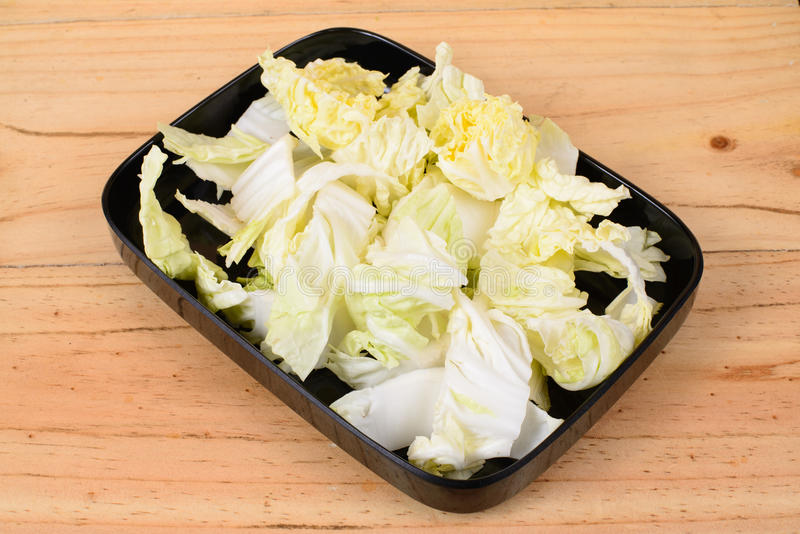 Napa cabbage. In black tray on wooden background stock image