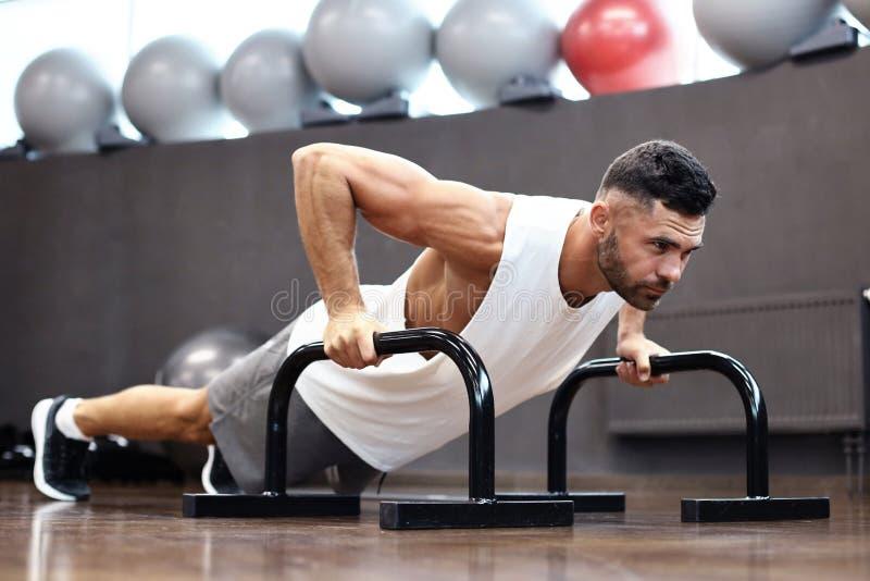 Napad i mięśniowy mężczyzna robi horyzontalnemu Ups z barami w gym fotografia royalty free