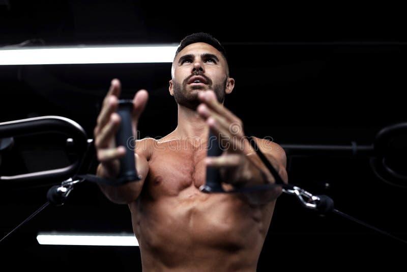 Napad i mięśniowy mężczyzna trenujemy piersiowych mięśnie na blokowym symulancie w gym zdjęcie royalty free