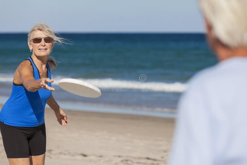 Starszego mężczyzna kobiety pary Frisbee przy plażą zdjęcia royalty free