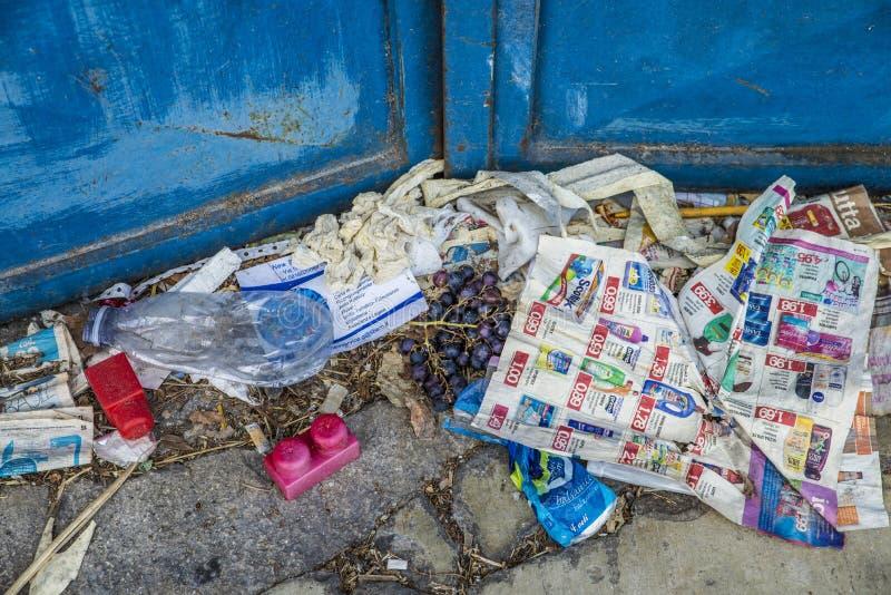 Napels, Italië - Augustus 11, 2015: Veel huisvuil en de druiven zijn op de kant van de weg voor een metaalpoort stock foto's
