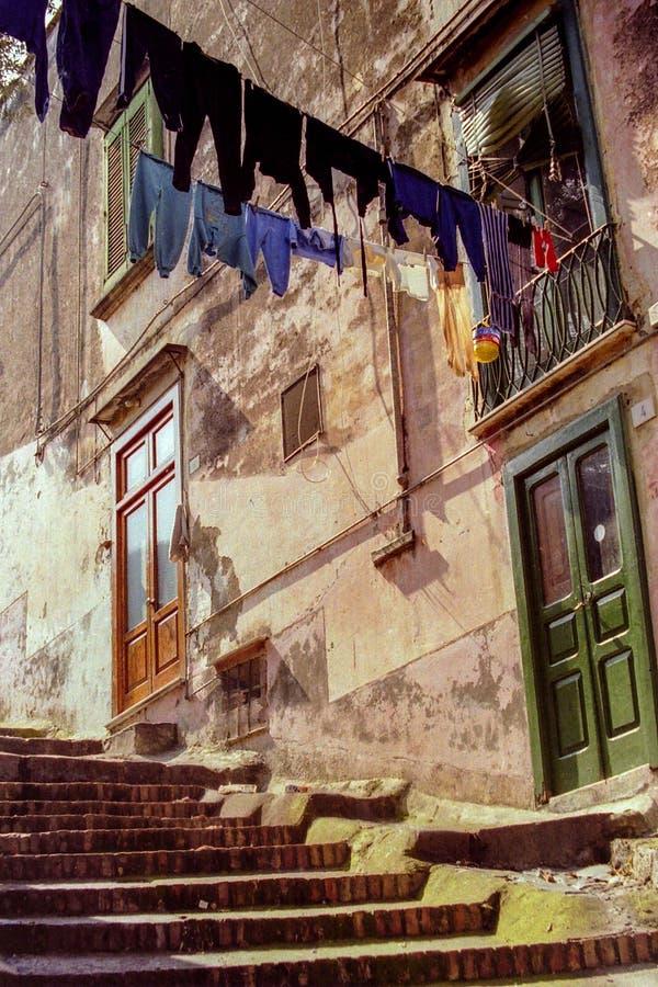 NAPELS, ITALI?, 1979 - een typische straat van Napels met kleren die uit tussen de huizen hangen te drogen stock foto