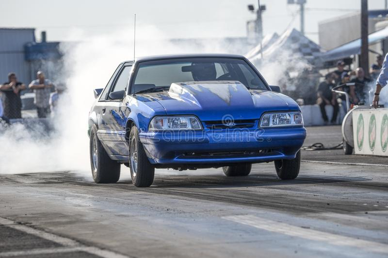 Mustang making a smoke show at the starting line on the track stock image