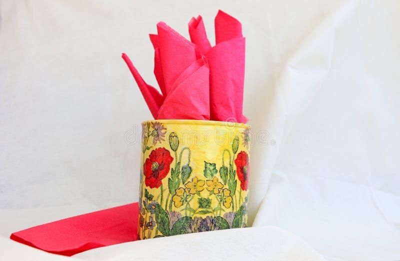 Napkin holder with red napkins. Deciratuve hand made table napkin holder with red napkins stock image