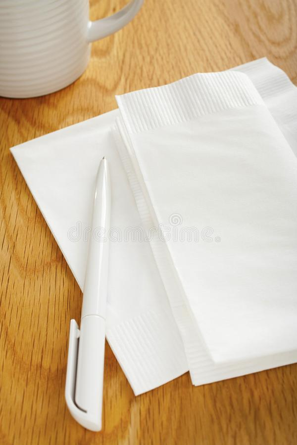 Napkin or Serviette and Pen on Table. White napkin or serviette and pen on oak surface, ideal for notes and phone numbers, and that great idea you had at the royalty free stock images