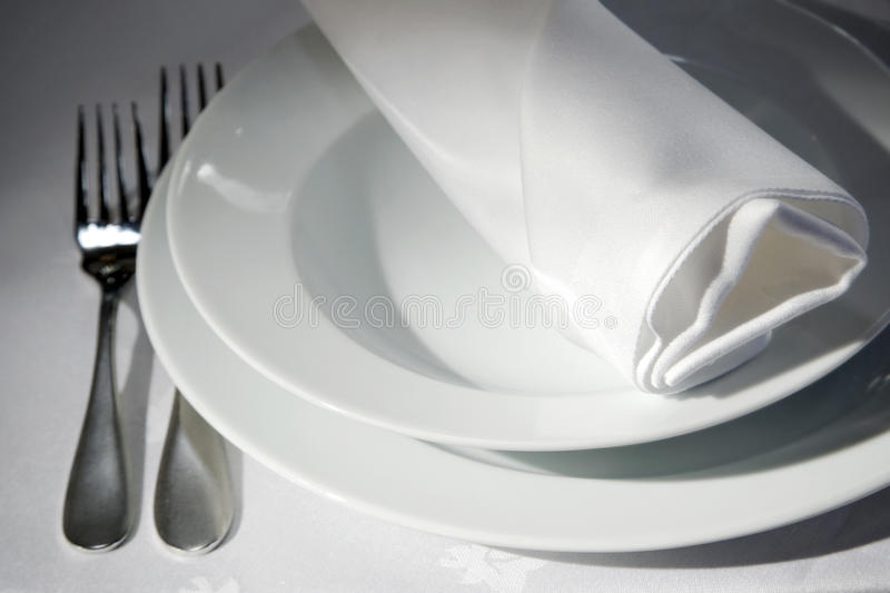 Napkin on tables. Dinner table detail with dishes, forks and focus on a napkin royalty free stock photography