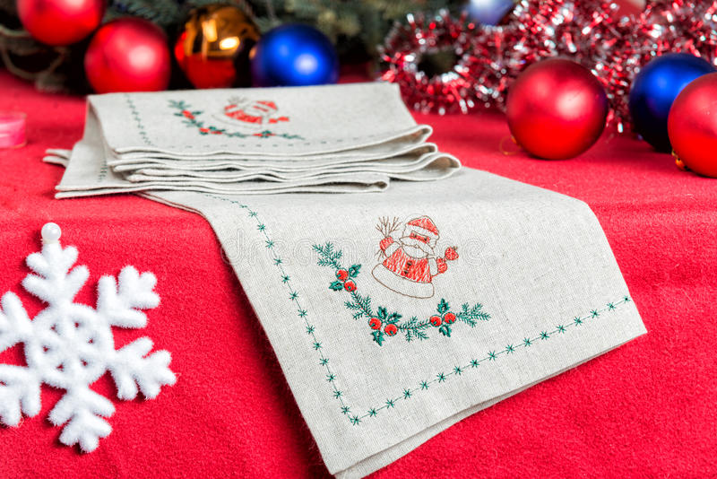 Napkins embroidered with Santa Claus for Christmas. Napkins with embroidery on the background of Christmas decorations and toys royalty free stock photos