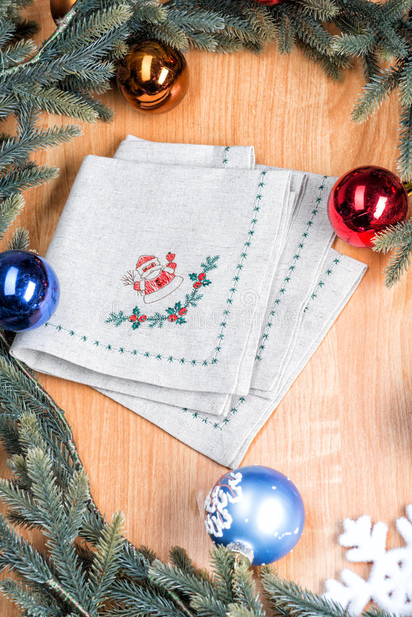 Napkins embroidered with Santa Claus for Christmas. Napkins with embroidery on the background of Christmas decorations and toys royalty free stock photography