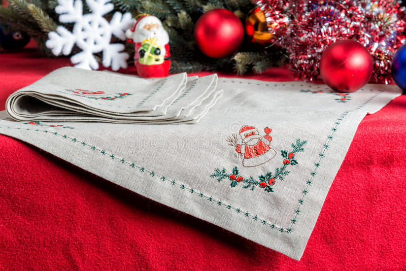 Napkins embroidered with Santa Claus for Christmas. Napkins with embroidery on the background of Christmas decorations and toys royalty free stock image