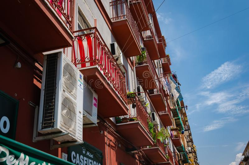 Exterior view of balconies of a building with red facade on blue sky background stock image