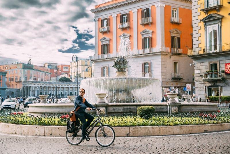 Naples, Italy. Adult Caucasian Man Tourist Riding On Bicycle Near Fontana del Carciofo stock photography