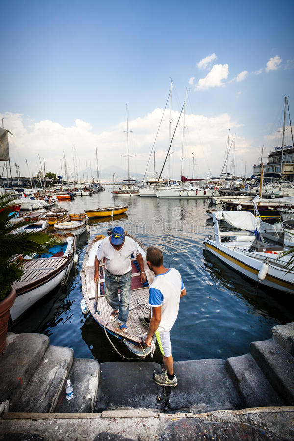 Naples, Italy. Ancient port city. Two fishermen are coming down from their small boat in the port of Naples. Many other boats and deep blue sky in the royalty free stock image