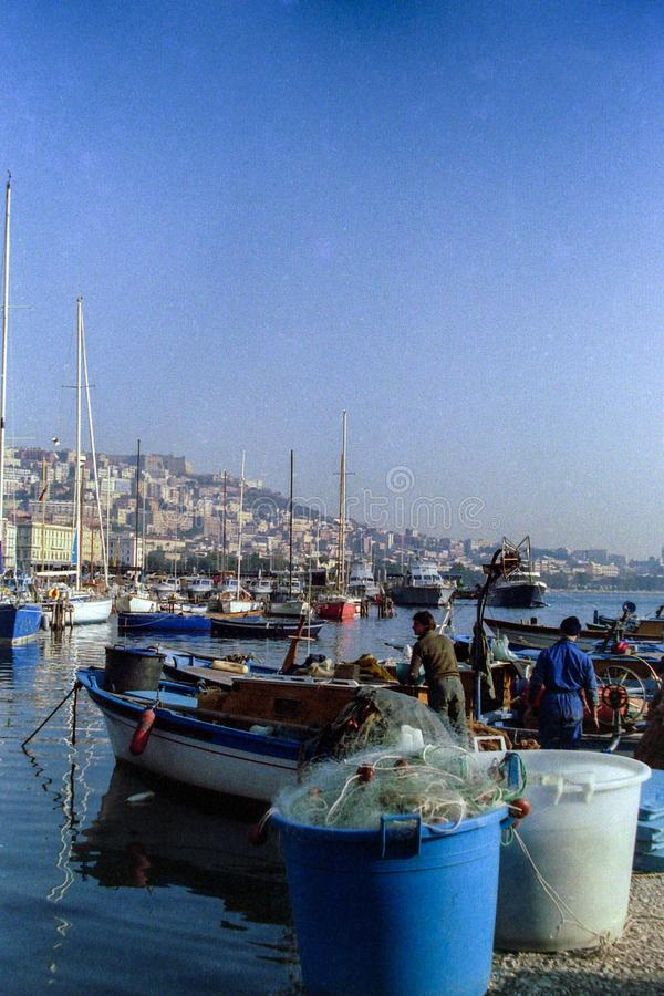NAPLES, ITALY, 1988 - Fishermen moor their boats in the port of Mergellina and place their nets after a day of hard work royalty free stock image