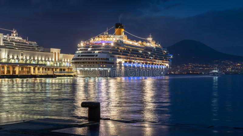 NAPLES, ITALY - NOV 5, 2018: Big white Costa Fascinosa cruise ship docked at the port of Naples at night. White cruise ship docked at the port of Naples royalty free stock image