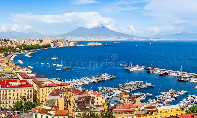 Naples city and port with Mount Vesuvius on the horizon seen from the hills of Posilipo. Seaside landscape of the city harbor and. Naples, Italy: Panoramic view royalty free stock photos