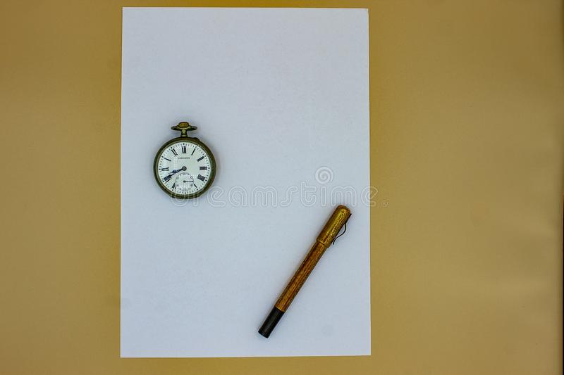 On a white sheet, an old gold fountain pen and an old pocket watch. The pen and the clock date back to the early 1900s, in fact yo stock photography