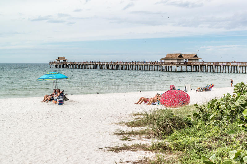 Naples pier and beach, Florida, USA. People on beach and pier in the city of Naples on the west coast of Florida, USA stock photography