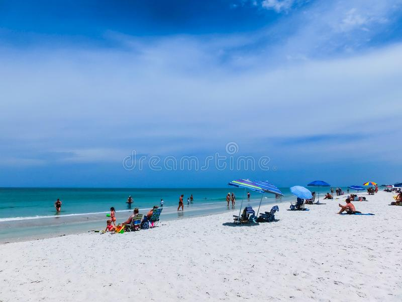 Naples, USA - May 8, 2018: Tourists enjoying the Vanderbilt beach in Naples, Florida. Naples is located on the Gulf Coast in southern Florida royalty free stock image