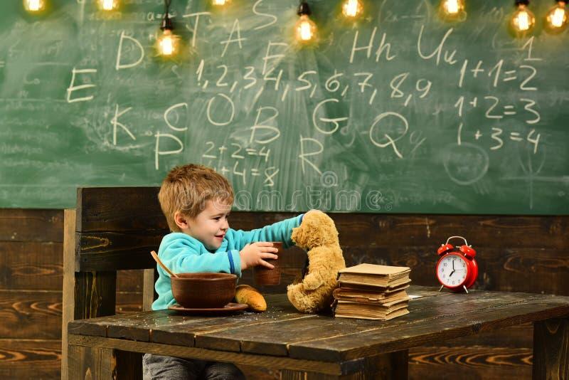 Napoju menu Małe dziecko karmy miś z wodą, napoju menu Chłopiec cieszy się napoju menu z zabawkarskim przyjacielem w sala lekcyjn obrazy royalty free