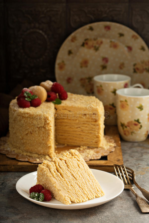 Napoleon cake with butterscotch frosting. Decorated with macarons royalty free stock image