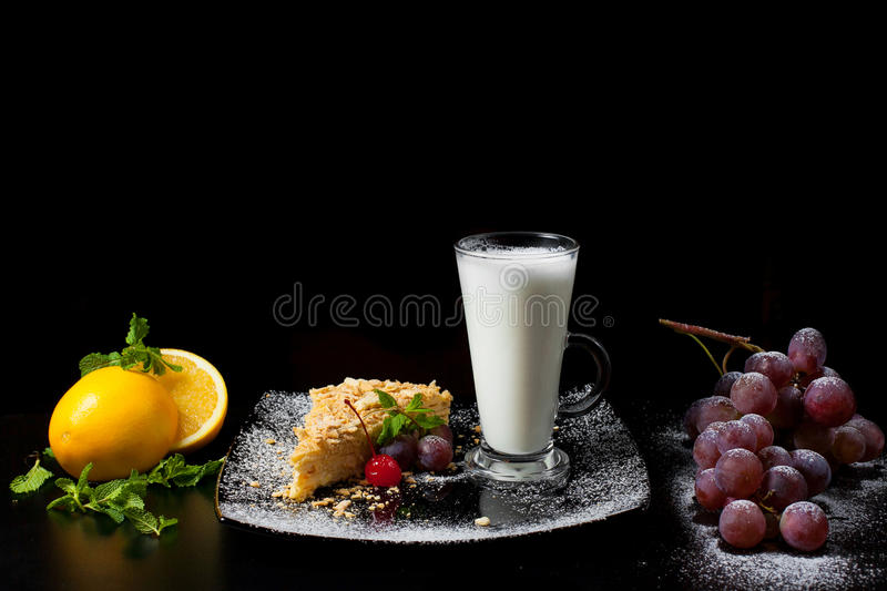 Napoleon cake with milk, grapes and oranges royalty free stock images