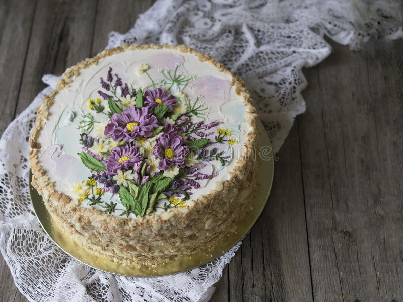 Napoleon cake with vanilla cream, decorated with buttercream flowers. Vintage style. Wooden background, lace napkin. Copy space, c royalty free stock photos