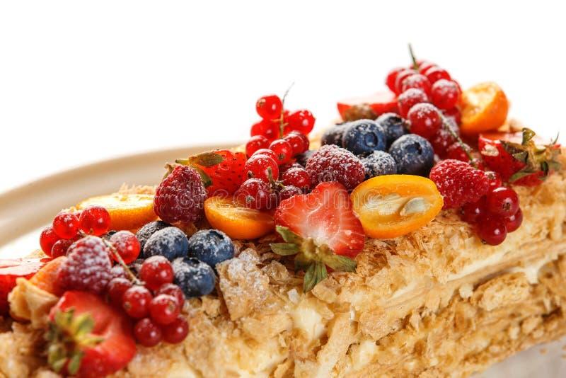 Napoleon kaka som dekoreras med bär på en platta på en isolerad vit bakgrund arkivbilder