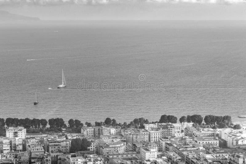 Napoli e mar Mediterraneo con la vista superiore bianca del traghetto e della barca in bianco e nero Spiaggia di Napoli sul tramo fotografia stock libera da diritti