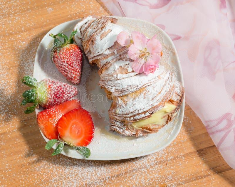 Napolitaans die dessert met suikerglazuursuiker wordt en met amandelbloesem en verse aardbeien wordt verfraaid bestrooid die royalty-vrije stock afbeeldingen