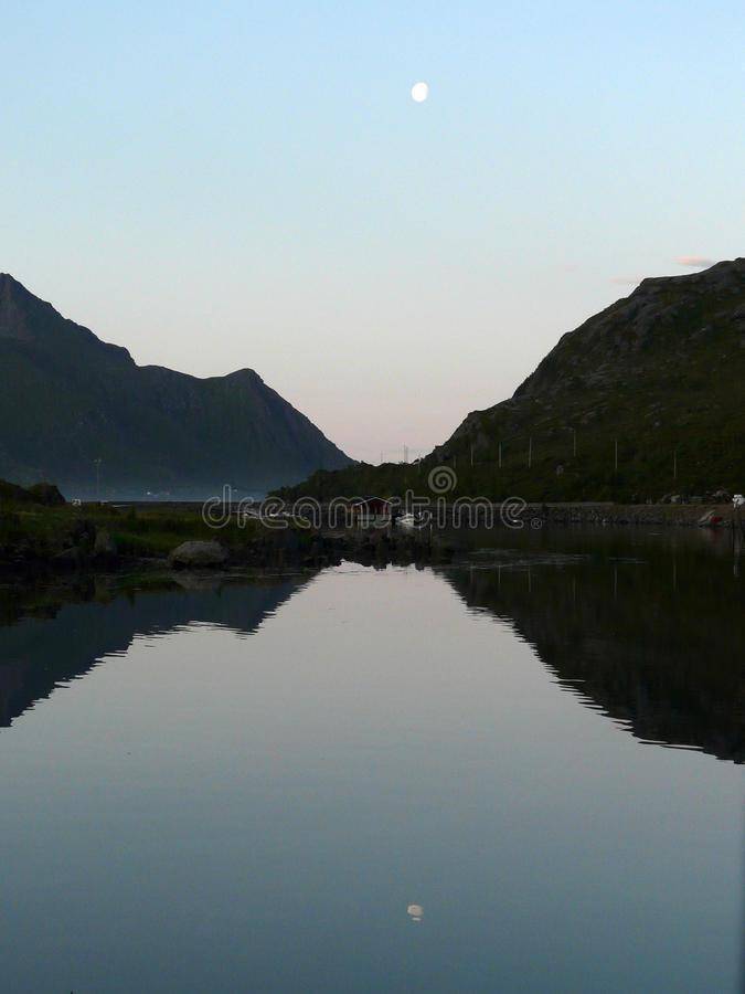 Napp i Lofoten mirroring. Houses of the small village of Napp i Lofoten mirroring in the fjord stock image