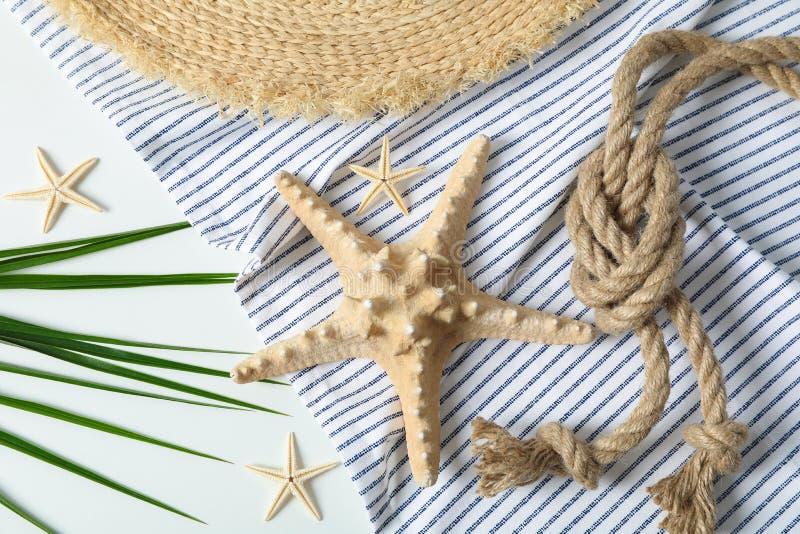 Nappe, chapeau de paille, étoiles de mer, corde de mer et palmettes sur le fond blanc, vue supérieure et plan rapproché photo stock