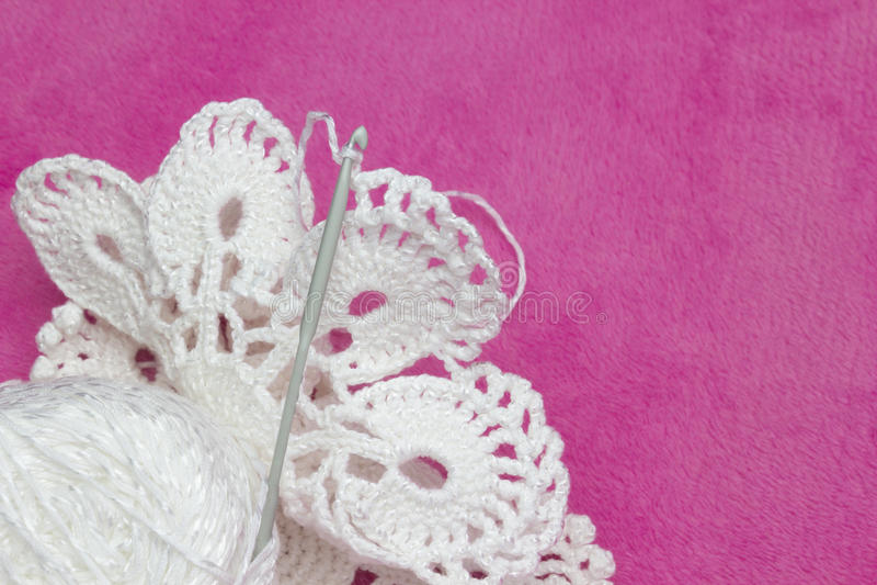 Napperon blanc de vintage Fils de coton pour le crochet de tricotage et de crochet Photo du processus de crochet sur le fond rose images stock