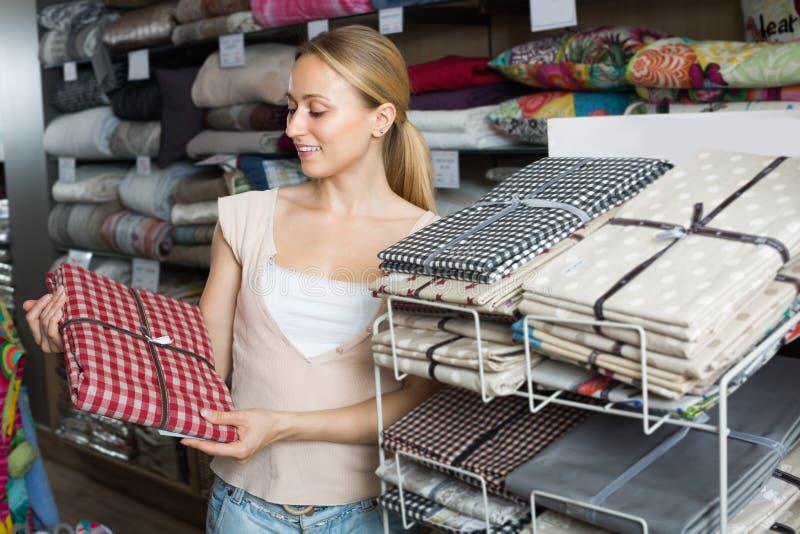 Nappes de achat de femme dans la boutique à la maison de textile photo stock