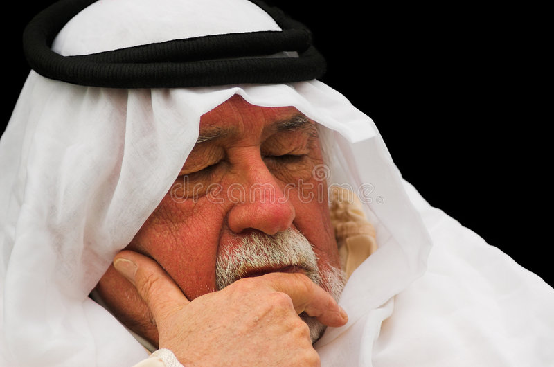 Napping. An older gentleman taking a nap, wearing Arabic headdress, a keffiyeh and agal royalty free stock photos