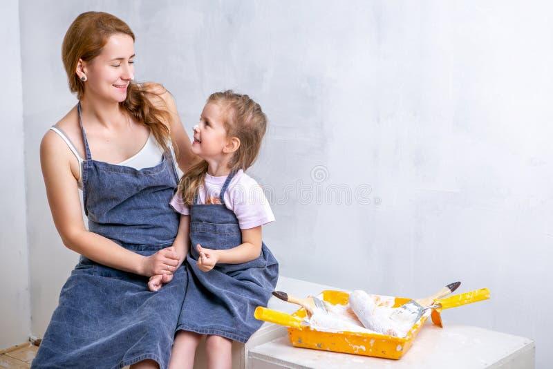 Naprawa w mieszkaniu Szczęśliwa rodziny matka, córka w fartuchach i malujemy ścianę z białą farbą Matka i córka siedzimy stronę obraz stock