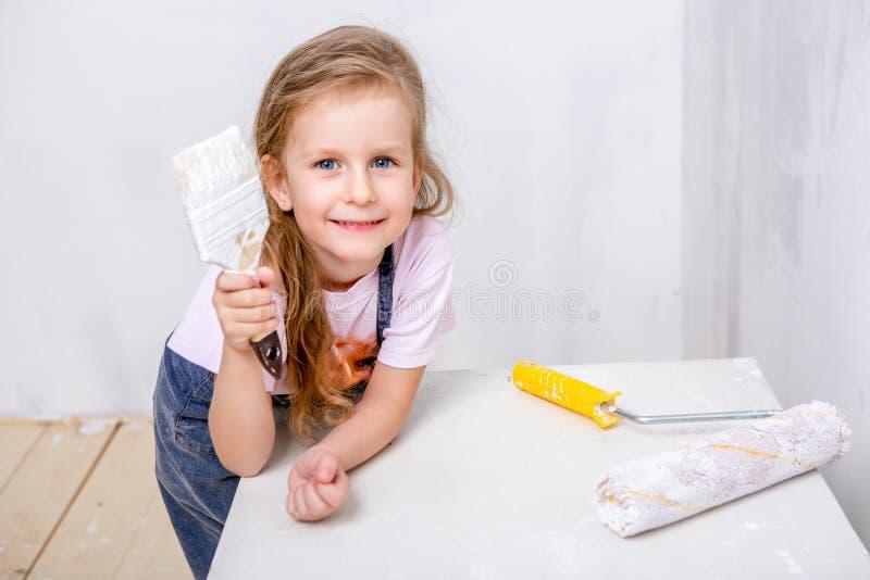 Naprawa w mieszkaniu Szczęśliwej rodziny macierzysta i mała córka w błękitnych fartuchach maluje ścianę z białą farbą Dziewczyna  fotografia royalty free