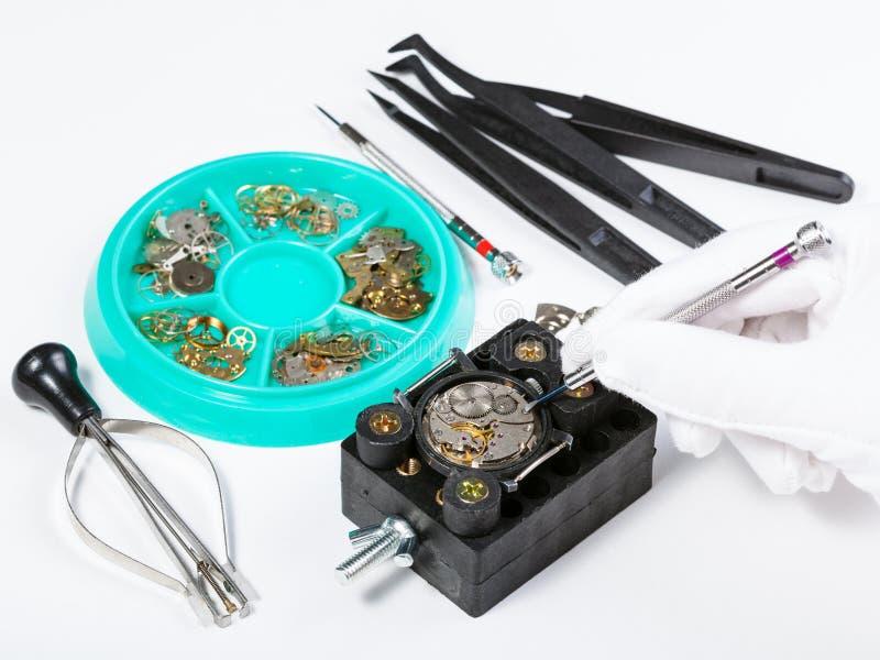 Naprawiać starego machinalnego zegarek na bielu stole obraz royalty free