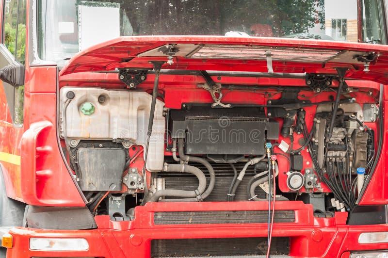 Naprawiania i naprawiania czerwieni duża ciężka ciężarówka z otwartym kapiszonem na ulicie jako miarowego utrzymania usługa semi, obraz royalty free
